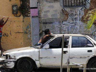 Dos niños destacan en medio de un paisaje dominado por unos muros que testimonian el paso del tiempo sobre la ciudad. Un automóvil, cansado de uso, se suma al entorno para evidenciar el transcurso de los años.